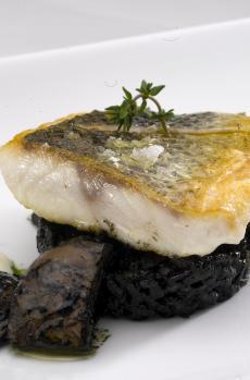 Lubina a la parrilla sobre arroz negro con calamares y salsa ali-oli